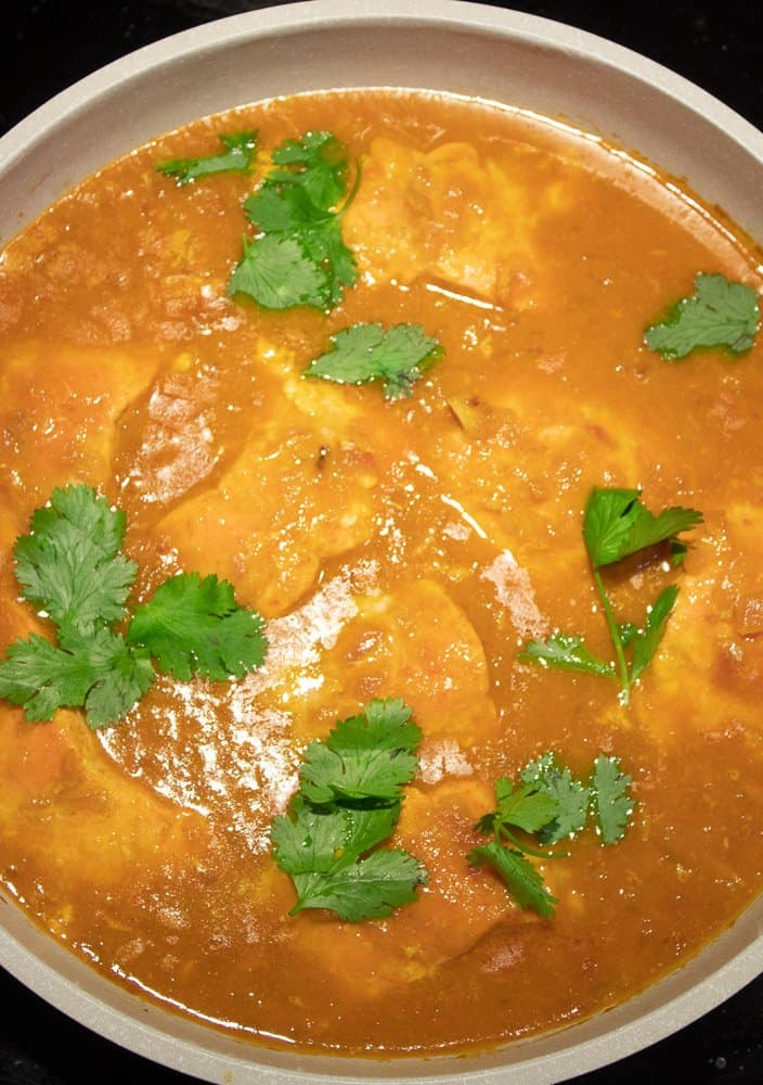Add Cilantro to cooked tomato Coconut Salmon Curry in the pan.