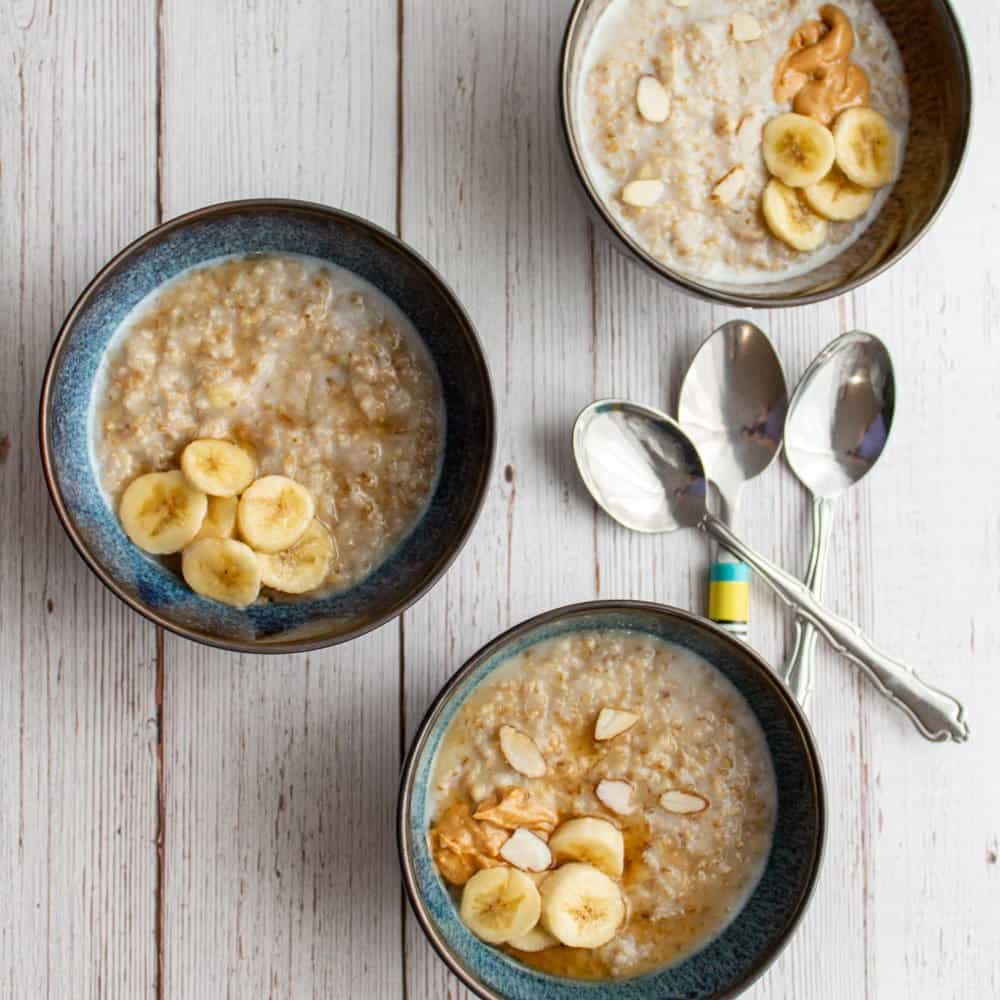 3 bowls of creamy banana steel cut oatmeal with toppings ready to serve with 3 spoons beside them.
