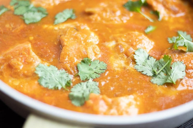 Close up image of Tomato coconut salmon curry Indian style in a pan.
