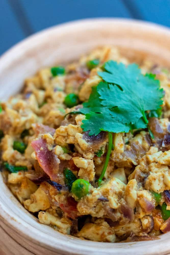 close up image of scrambled tofu matar masala ready to serve in a pot with cilantro on top