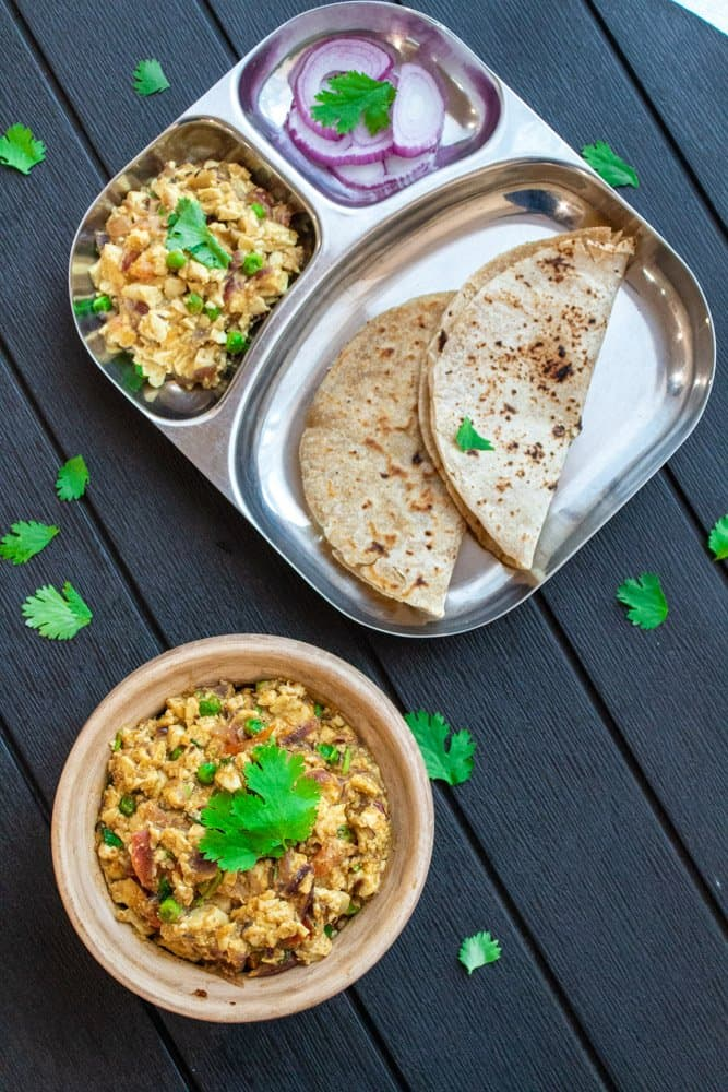 Indian style scrambled tofu curry in a serving dish and also served in a stainless steel partitioned plate beside the serving dish along with flat bread and sliced red onions