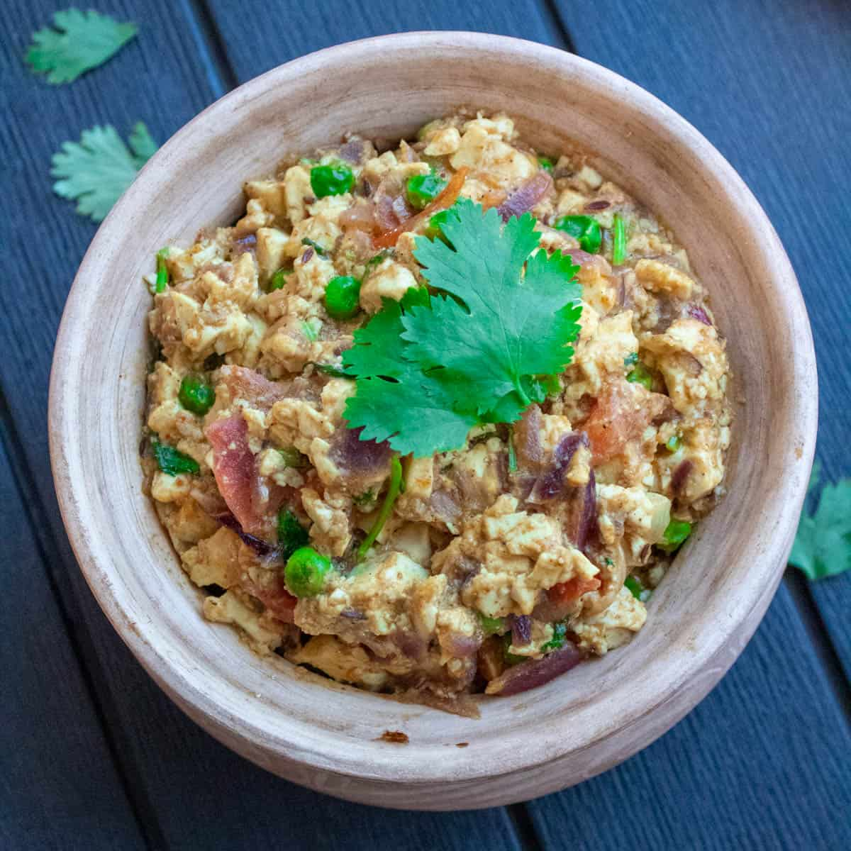 Indian style Scrambled tofu curry in a serving pot garnished with cilantro on top