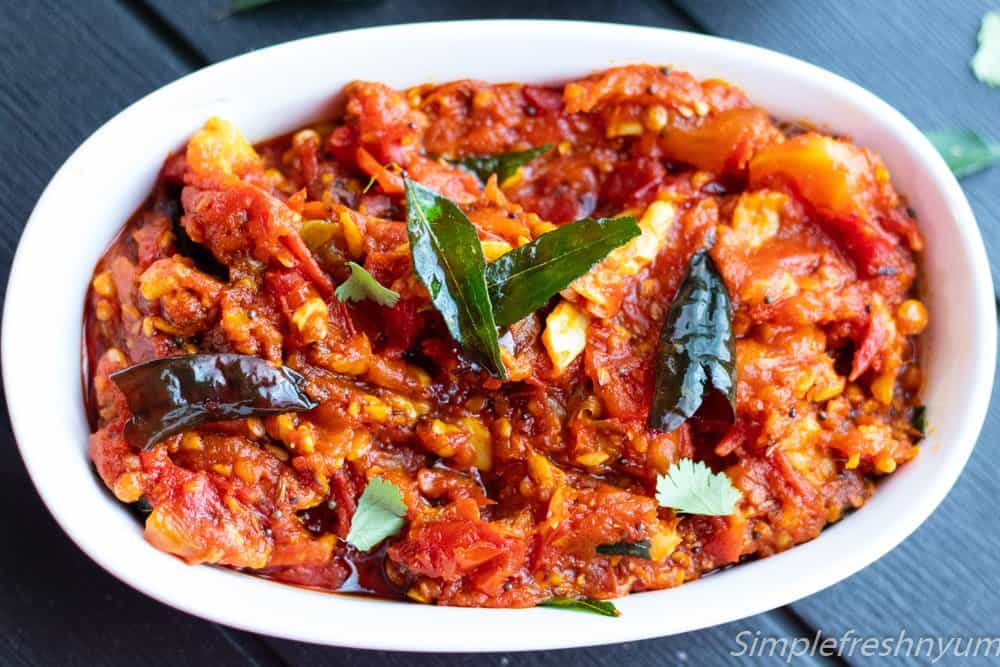 Tomato pachadi /Tomato chutney recipe close up image in a white serving dish with curry leaves and red chillies on top.