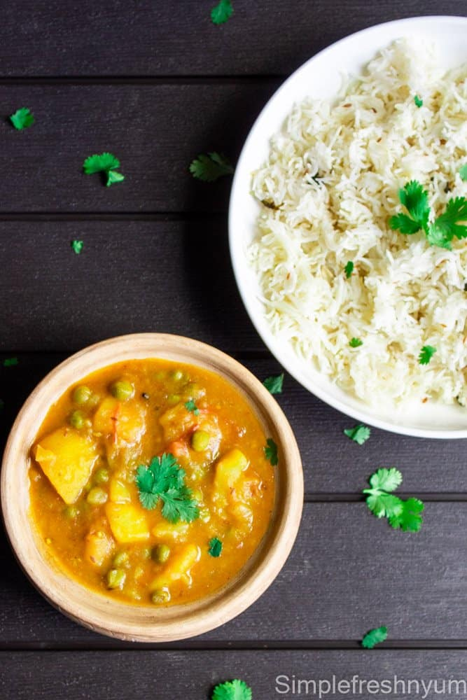 Aloo Matar Curry in a serving pot with jeera rice on the side in a white plate with cilantro garnished on top.