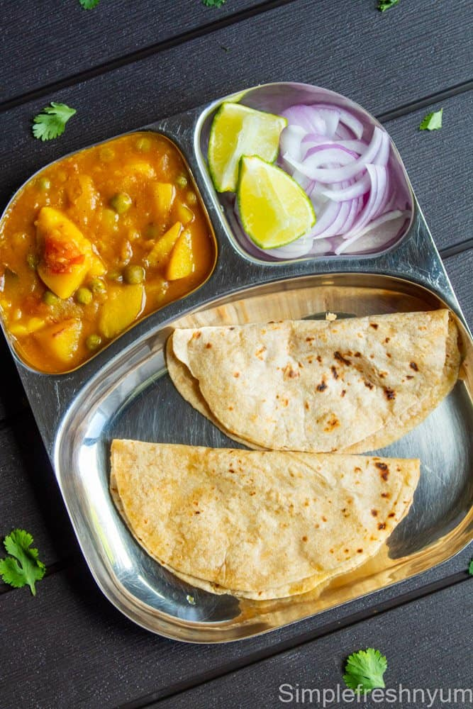 Aloo Matar curry served with 2 roti and onions and lemon in a steel plate.