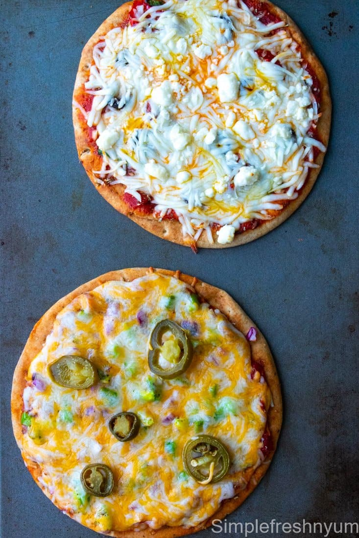 Greek Inspired Pita Pizza and Mexican Inspired Pita Pizza after baking on a sheet pan.