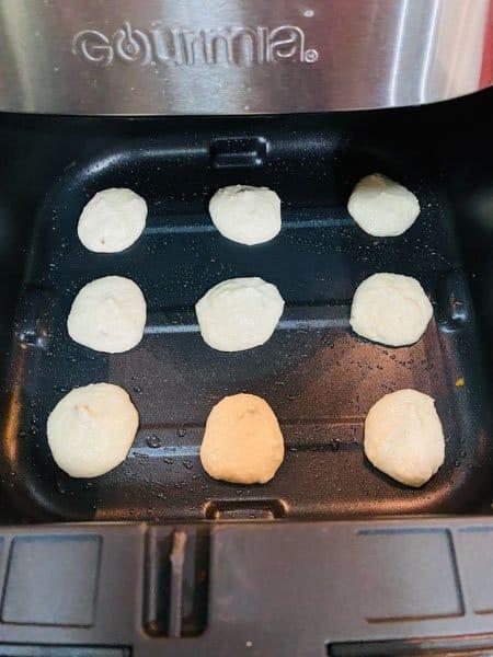 Dropped Medu vada batter in small dollops inside the air fryer basket