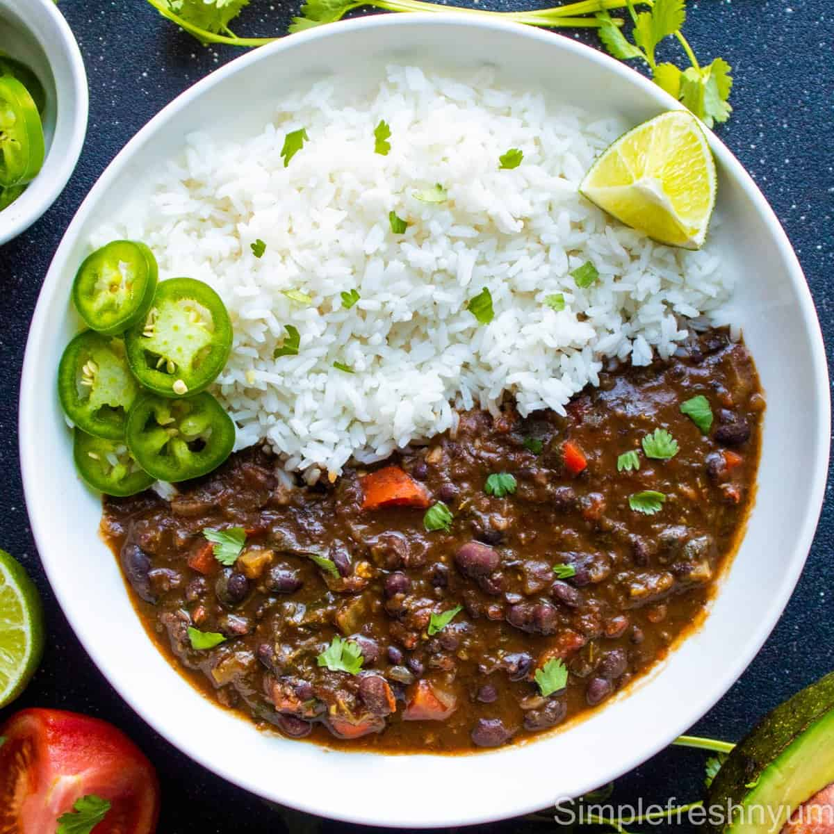 Black bean soup served with rice on a white plate with jalapeno slices and lemon wedge on the side with an avocado half, tomato slice and cilantro on the side of the plate
