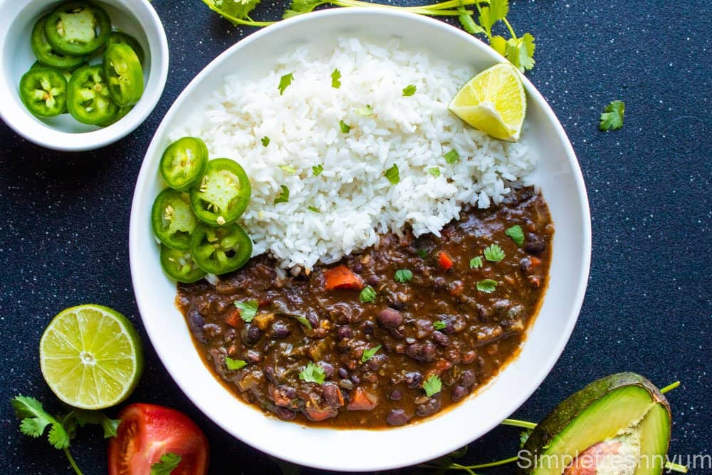 Black bean soup served with white rice in a white plate with Jalapeno slices and lemon slice with a white bowl of jalapeno slices on one side, half cut avocado on another side and half cut lemon and tomato on third side.