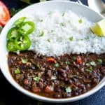 Black bean soup served with white rice with jalapeno slices and a lemon wedge on the side