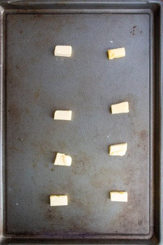 Cubes of butter spread on the sheet pan to put in the oven to be melted