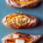 3 baked sweet potatoes with different toppings in each on a baking sheet. One topped with butter cube, one with coconut, raisin and nut topping and another one with butter cube and cinnamon sugar.