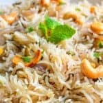 Close up picture of Bagara rice on a white plate with mint and roasted cashews garnished on top