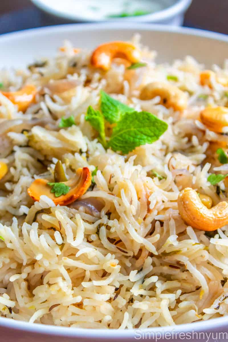 Bagara rice served in a white plate with roasted cashews and mint on top and a bowl of raita on the side.