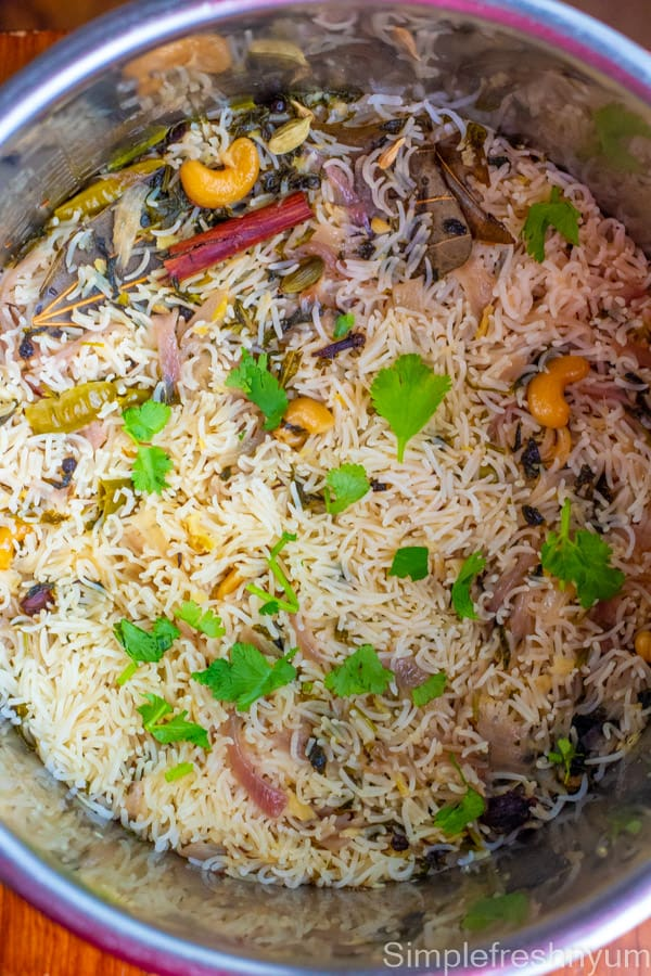 Cooked bagara rice in the instant pot inner pot ready to be fluffed and served. It is garnished with cilantro on top
