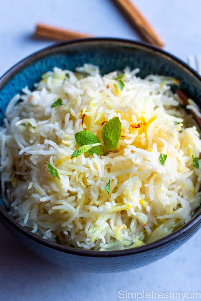 Cooked basmati rice in a black serving bowl with mint and saffron garnished on top.