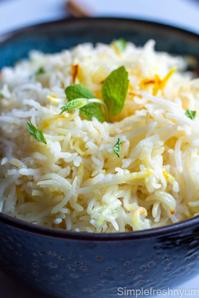 close up picture of cooked Basmati Rice in a black bowl with Mint garnished on top