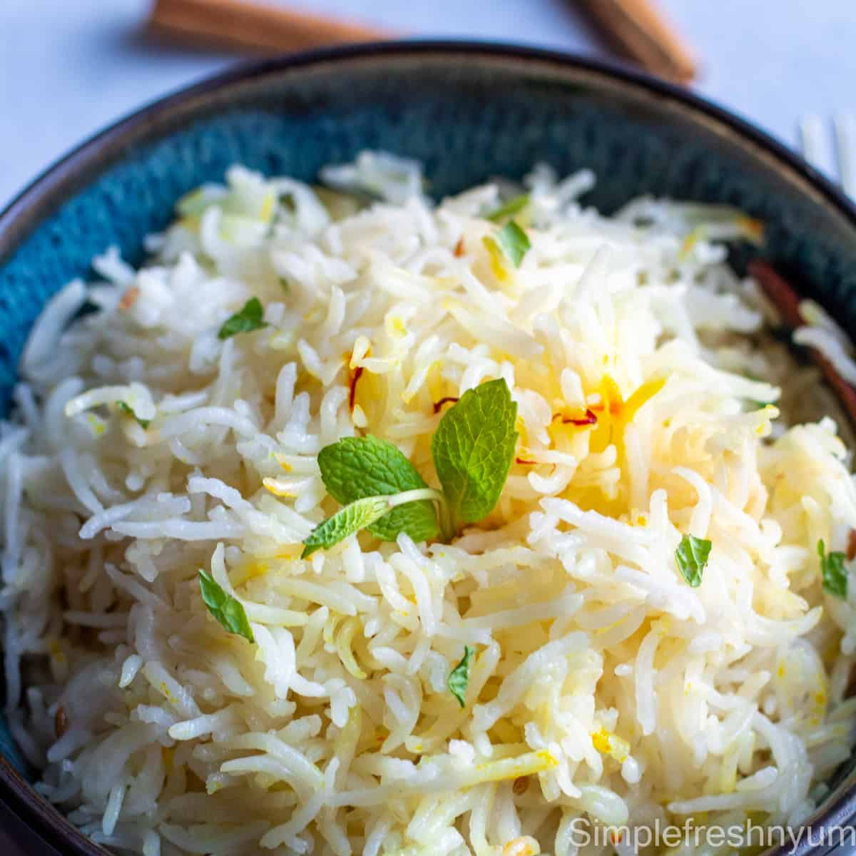 close up picture of cooked rice in a black bowl with mint garnished on top