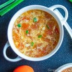 Egg drop soup in a white bowl with green onions garnished on top on a black surface