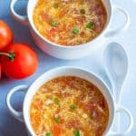 Tomato egg drop soup in white bowls with chives garnished on top on a white surface