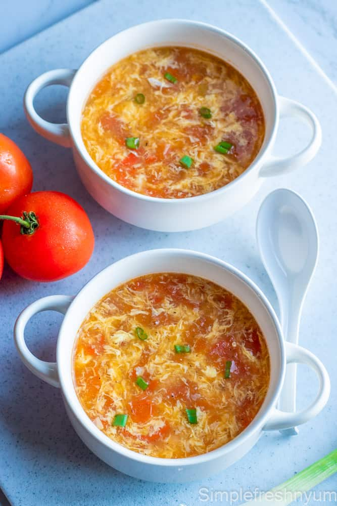 Egg drop soup served in two white soup bowls with a soup spoon, on the vine tomatoes and green onion on the side.
