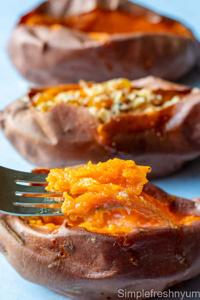 Close up picture of the baked sweet potato pulp on a fork and baked sweet potatoes with toppings in the back ground on a white surface.