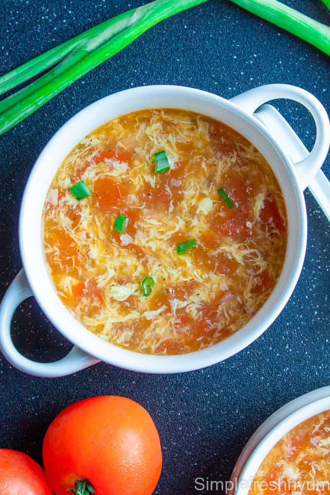 Egg drop soup served in white bowls with green onions garnished on top and tomatoes and green onion stalks on the side