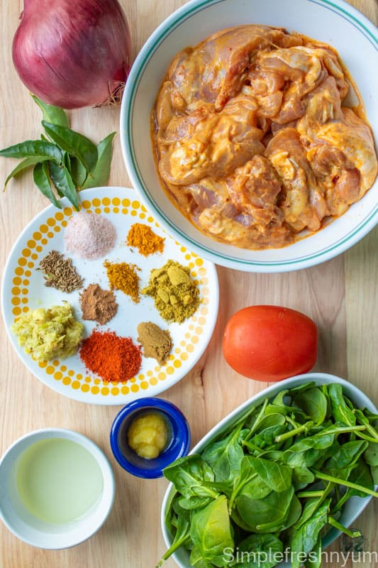 Picture of all the ingredients required to make chicken palak taken on a light wooden colored chopping board.