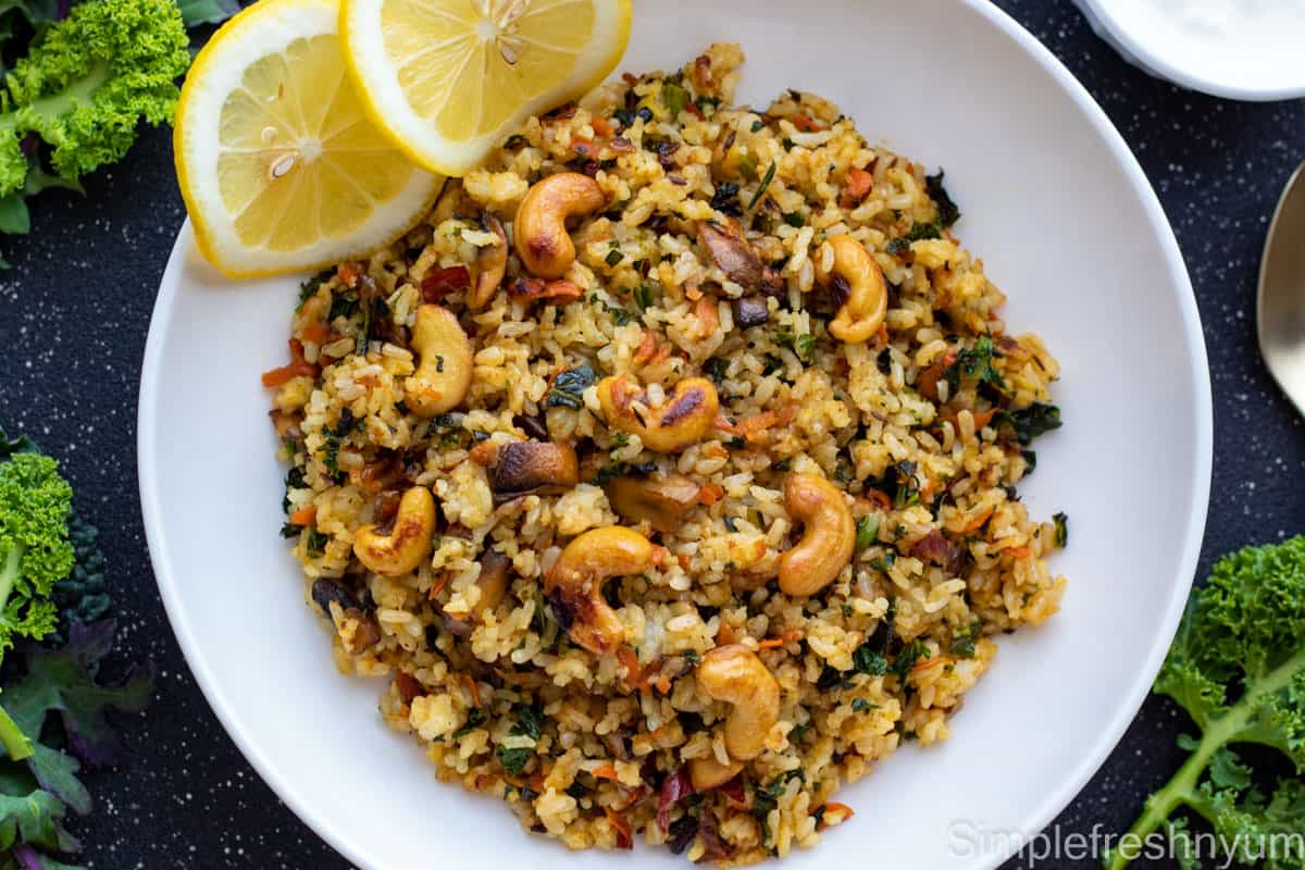 Kale rice with cashew nuts garnished on top served on a white plate with lemon slices. There is a spoon on one side and fresh kale to the side of the plate. Plate is on a black surface with white dots.