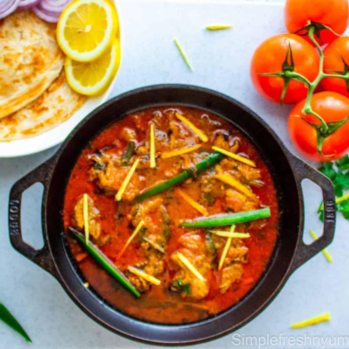 Chicken Karahi in a black cast Iron Wok garnished with thinly sliced jalapenos and ginger juliennes. There are some vine tomatoes on the side and a white plate of paratha with lemon slices on the other side.