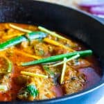 Chicken Karahi served in a black cast iron wok ( Karahi) with slices of jalapenos and ginger juliennes on the top