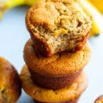 Almond flour muffins stacked on top of each other with a half eaten muffin on the top of the stack. Bananas in the back ground.
