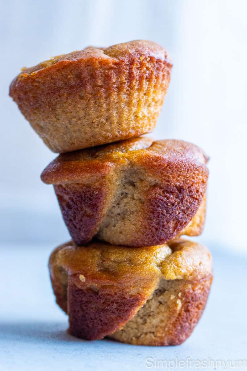 2 Rose shaped and 1 round almond flour muffins stacked on top of each other on a white surface