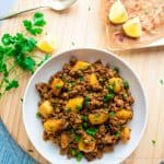 Aloo Kheema Matar served on a white plate with a plate of paratha ( flat bread) and lemon slices on one side and cilantro on the other on a wooden cutting board.