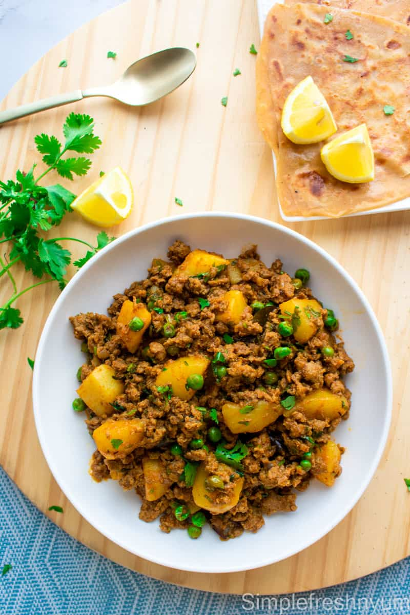 Aloo Kheema Matar served in a white plate with cilantro garnished on top and a plate of parathas and lemon slices on one side and cilantro bunch on the other on a wooden cutting board.