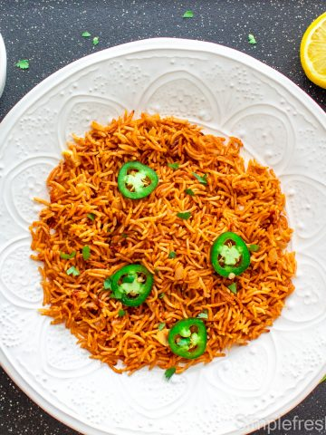 Arroz Rojo/Spanish rice served in a round white plate with jalapeno slices and cilantro garnished on top. There is a lemon on one side and a bowl of black bean soup on another side.