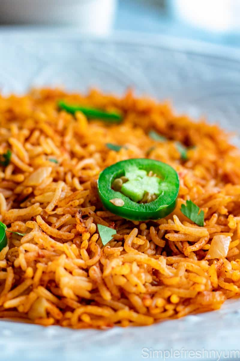 Close up image of Arroz Rojo/Spanish rice served in a round white plate with jalapeno slices and cilantro garnished on top.