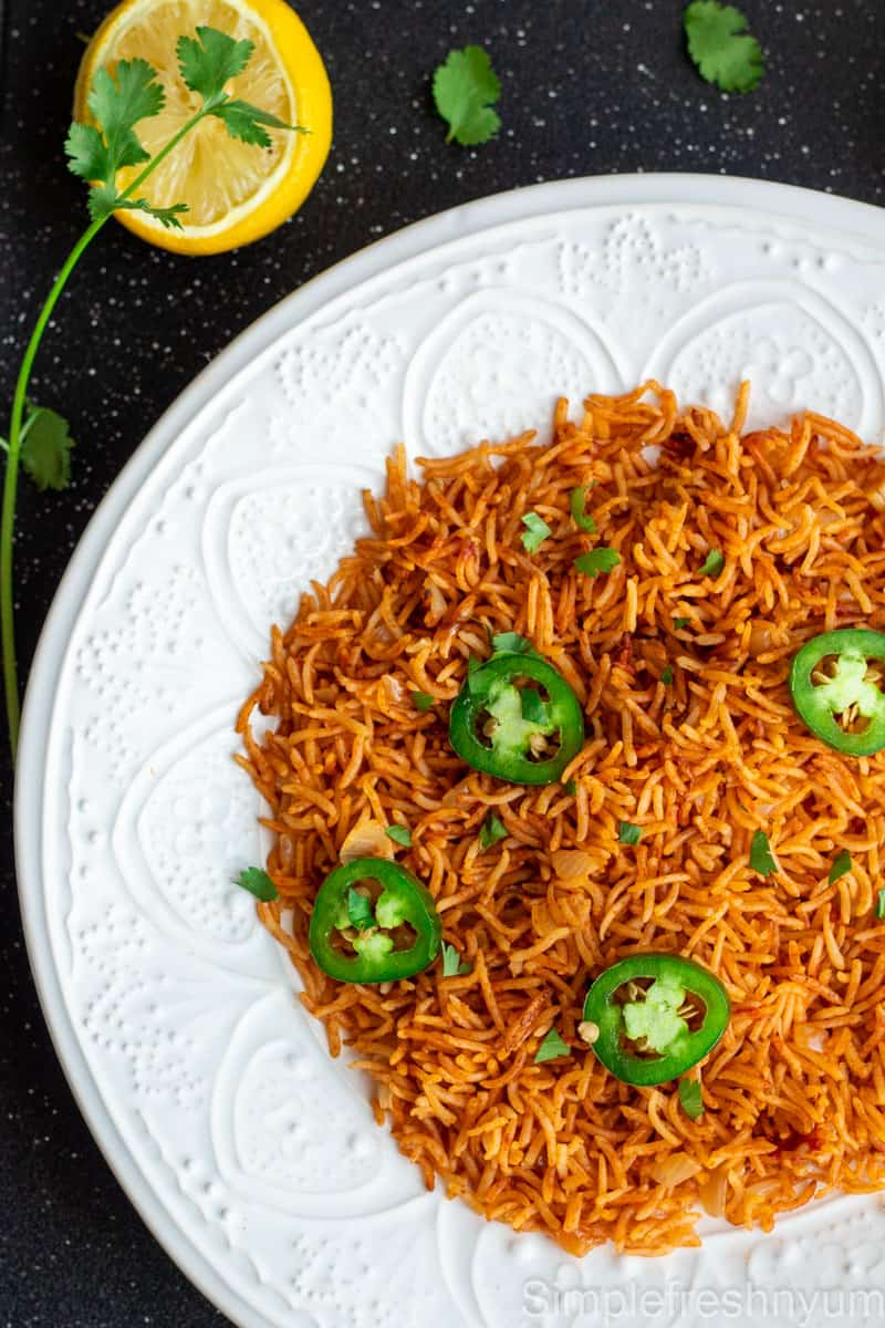 Arroz Rojo/Spanish rice served in a round white plate with jalapeno slices and cilantro garnished on top and lemon on the side.