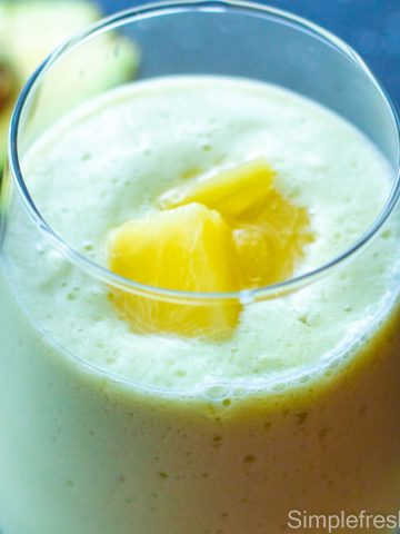 Close up image of Avocado pineapple smoothie in a glass with pineapple pieces garnished on top and a half avocado on the side.