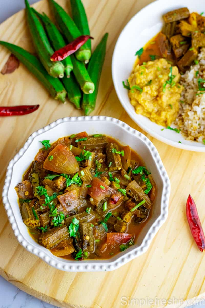Bendakaya pulusu in a white serving bowl on a light colored wooden board. There is a plate served with mix of white and brown rice, plain dal and Okra curry on one side and a bunch of Okras on the other side with red chillies strewn around the board.