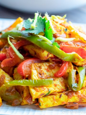 Close up image of Paneer Jalfrezi on a white plate with cilantro garnished on top