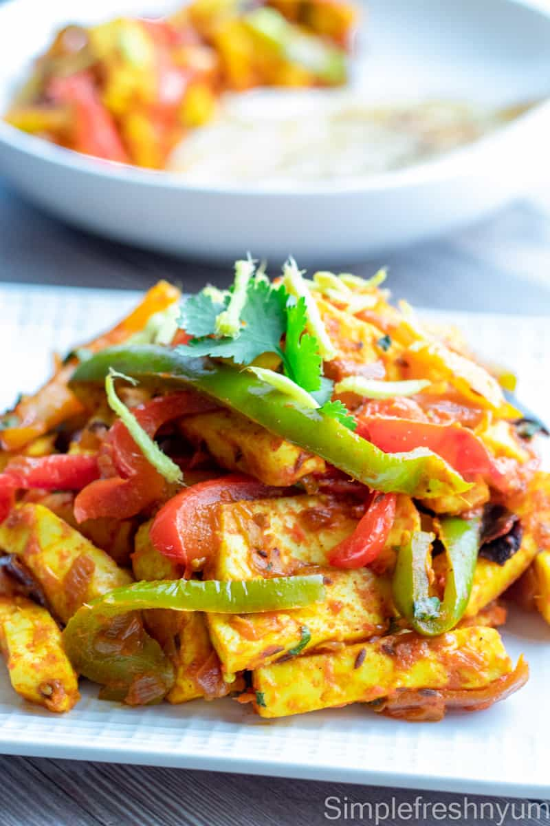 Paneer Jalfrezi served on a white serving plate with fried Ginger juliennes on top and a plate of Malabar Parotta on the side.