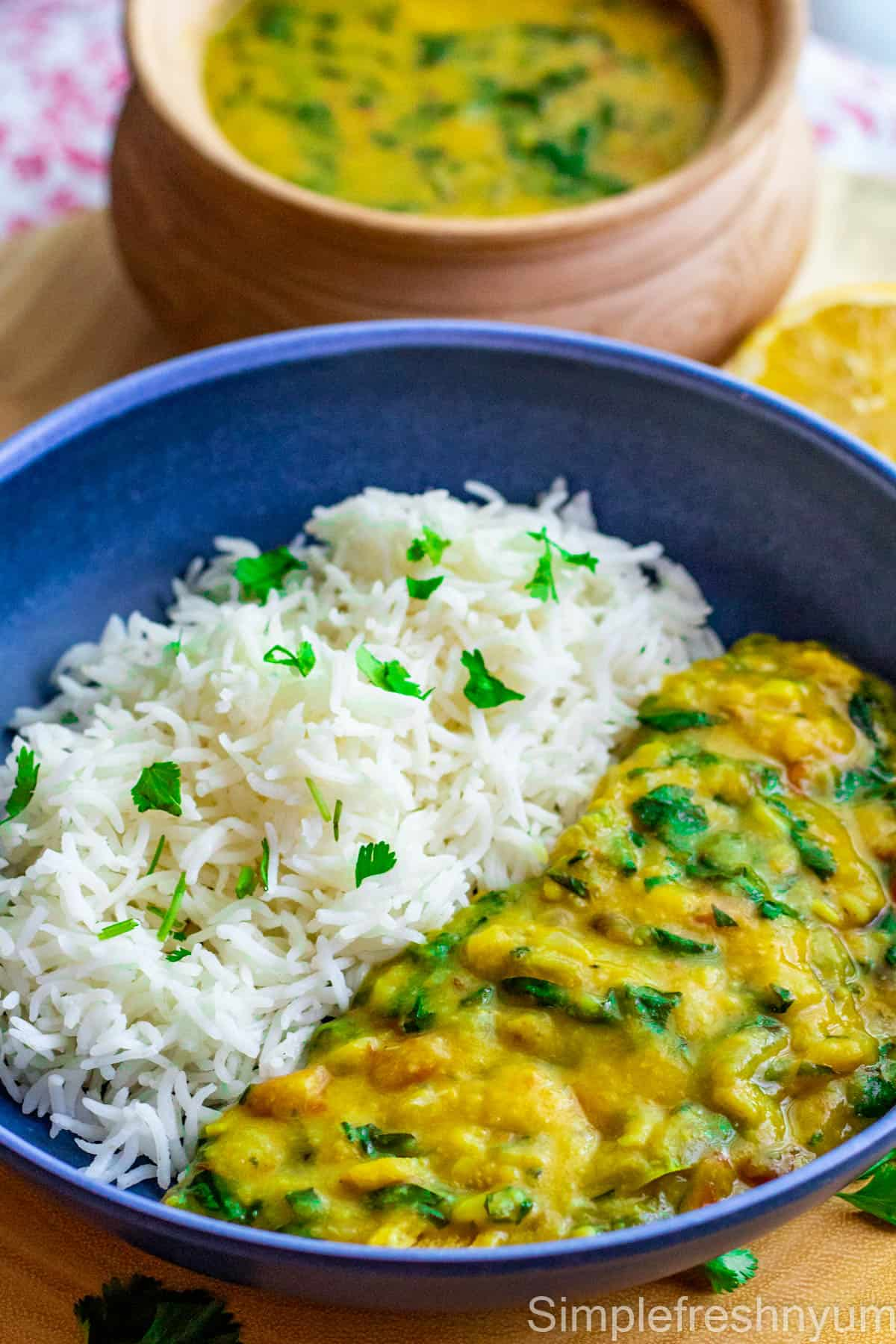 Dal Palak served with white rice in a blue plate with cilantro garnished on top. Dal Palak is in a serving dish in the back ground.