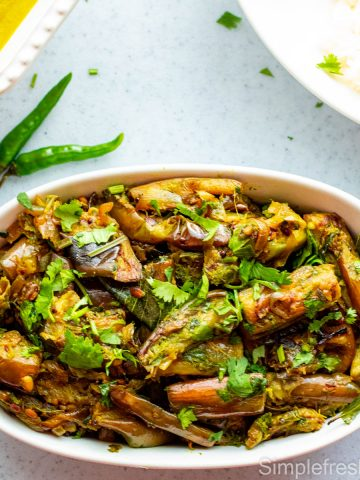 Brinjal fry in a white oval serving dish with two thai green chillies on the side and cilantro garnished on top