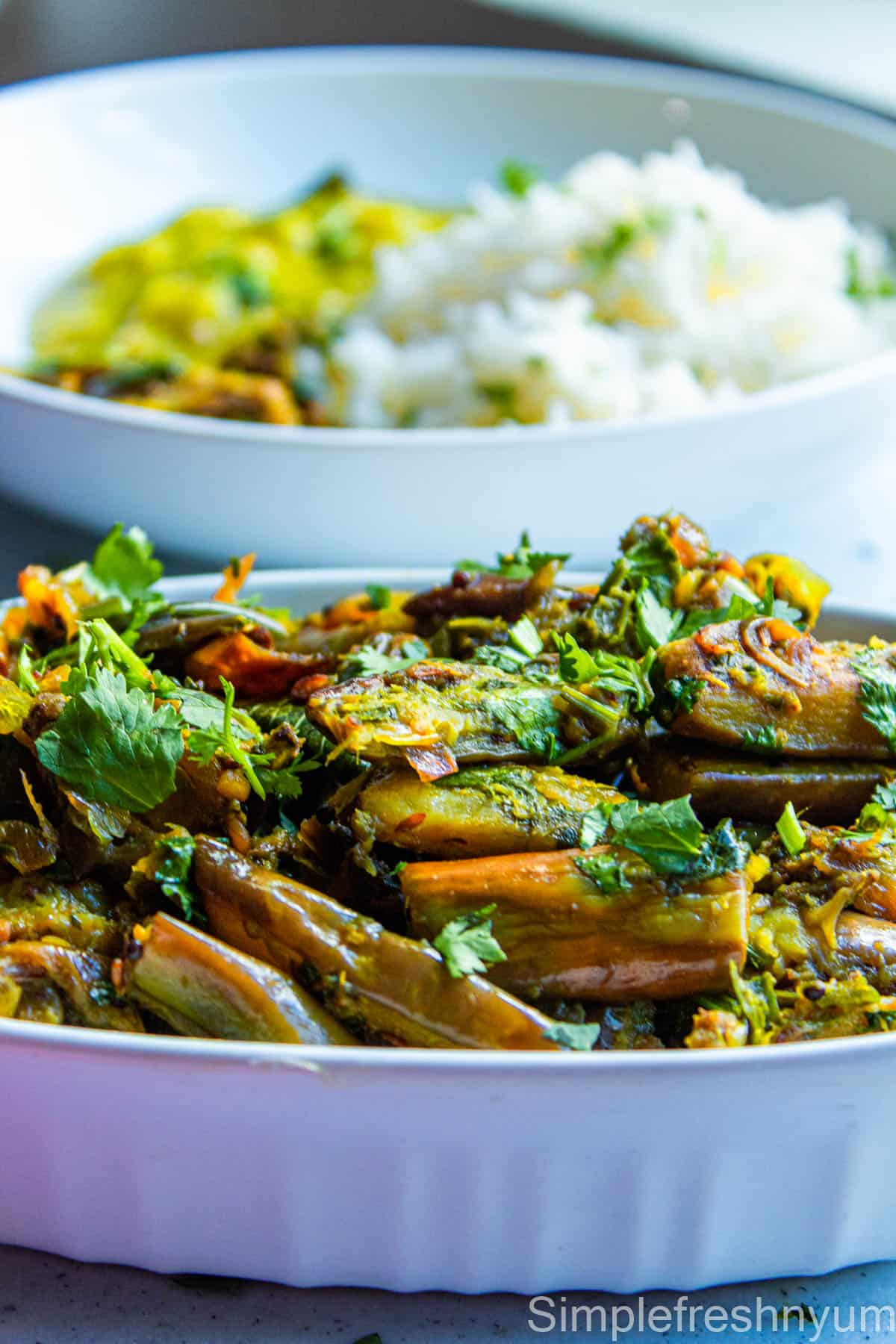 Brinjal fry served in a white oval serving dish with a plate served with rice, brinjal fry and dal in the background. Cilantro is garnished on top.