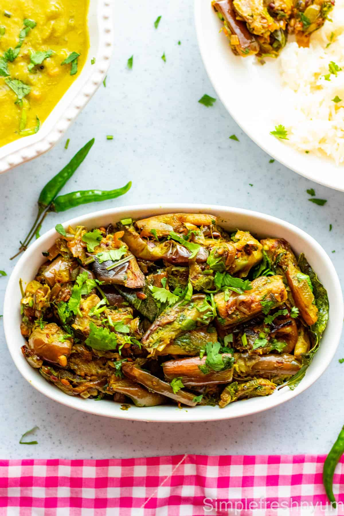 Brinjal fry served in a white oval serving dish with a dish of dal on the side and a plate served with rice, brinjal fry and dal. Cilantro is garnished on top.