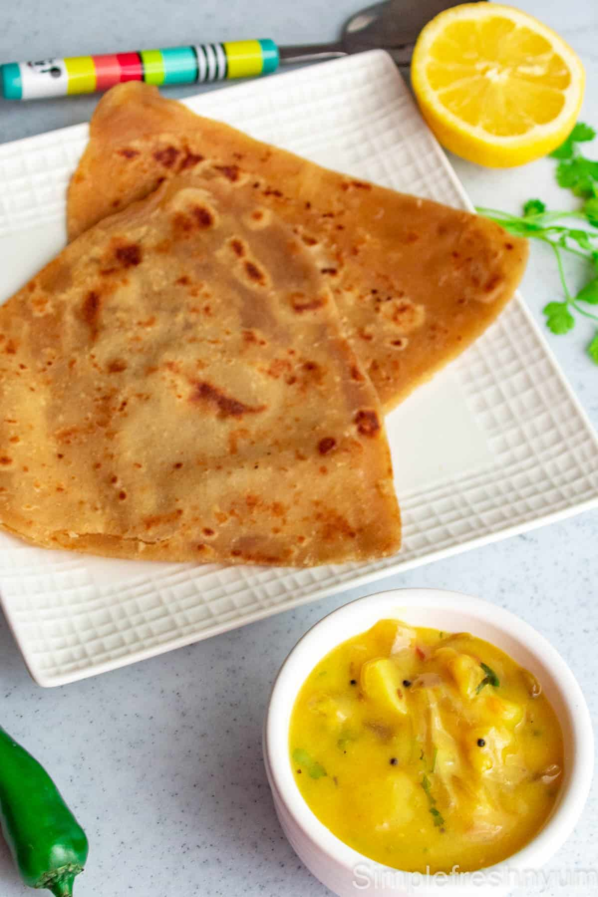 Two chapathi served in a white square plate with a white bowl of bombay chutney on the side and half lemon, an jalapeno and cilantro are on the sides too.